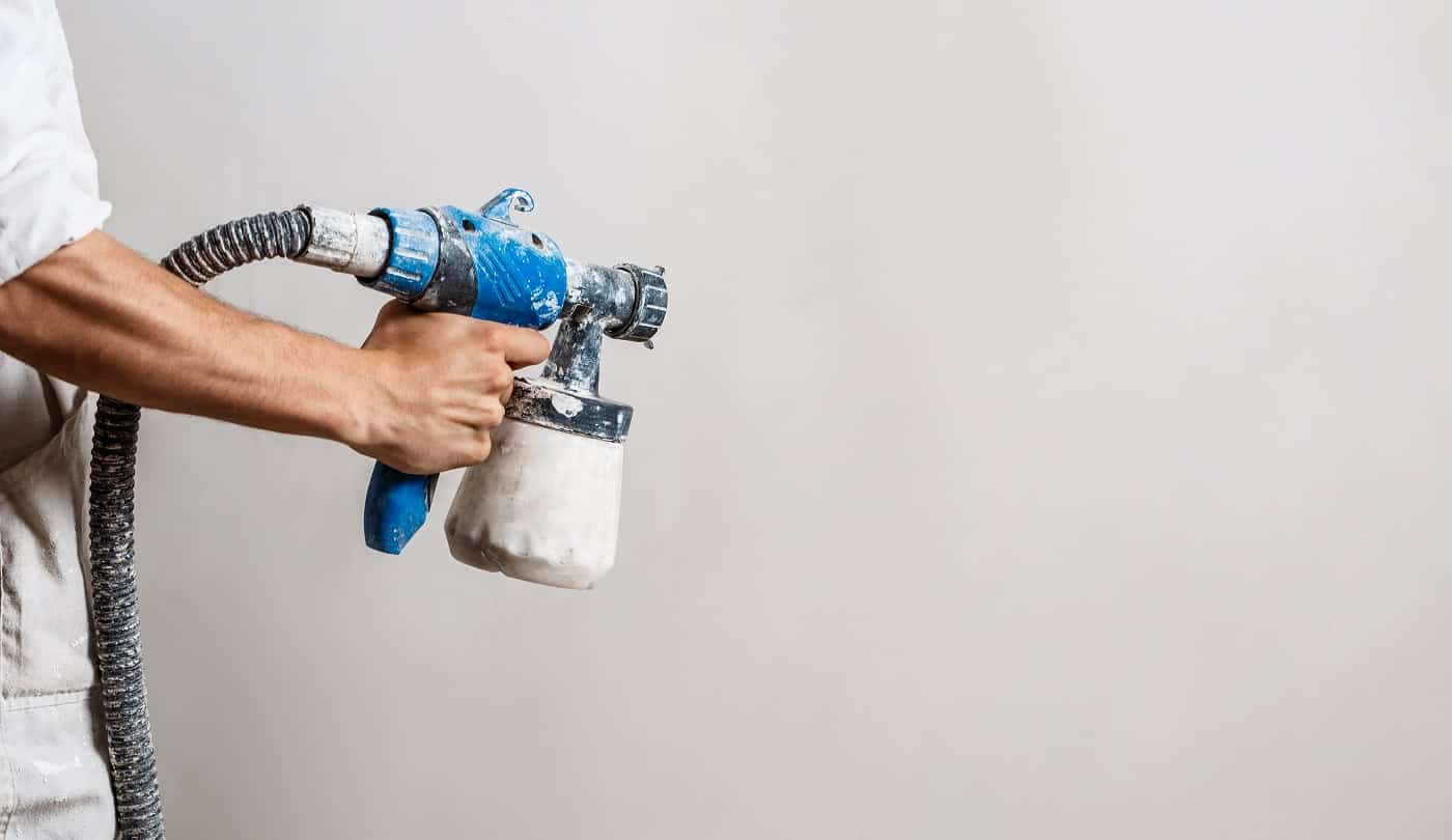 Worker painting wall with spray gun in white color. Copy space.