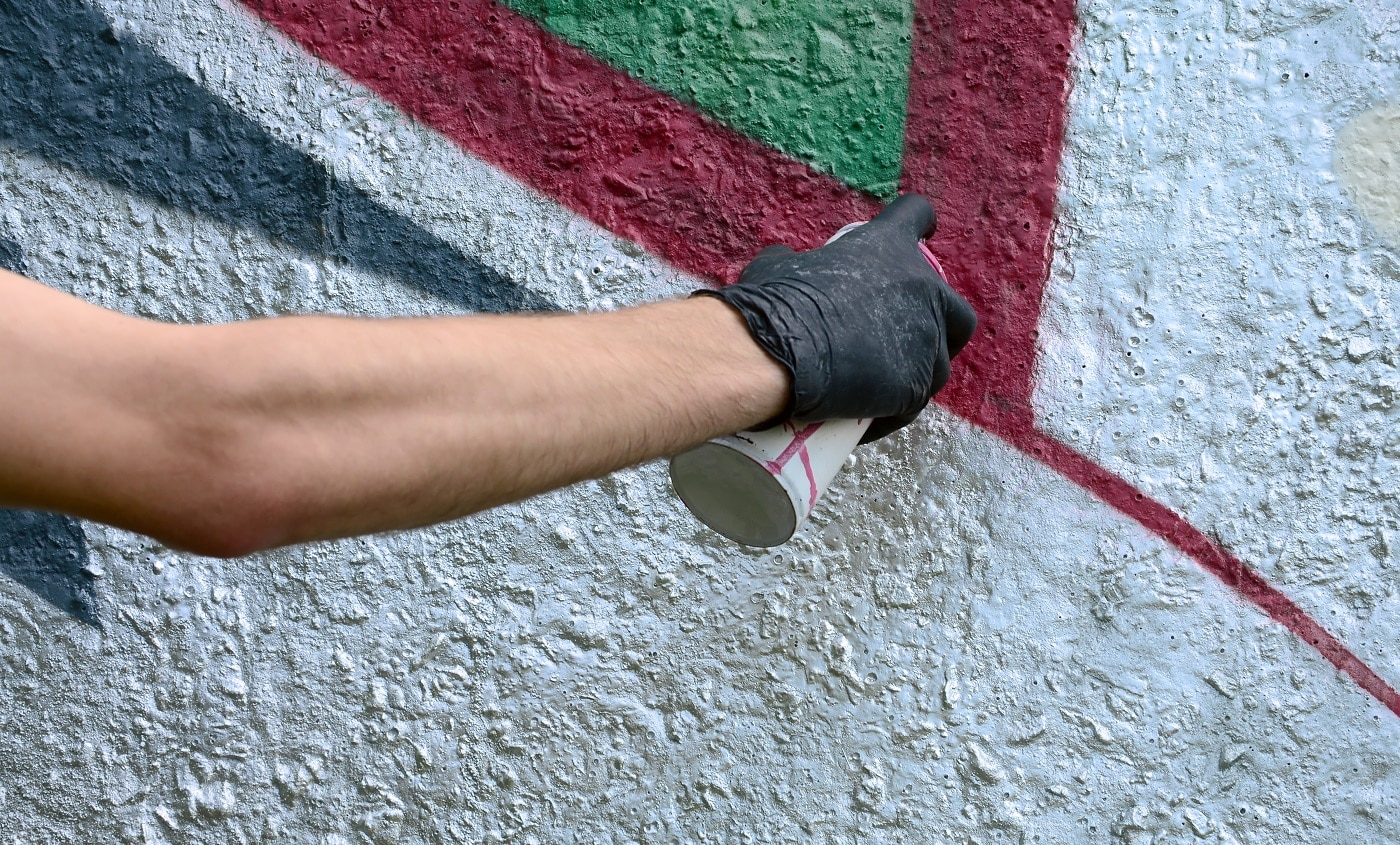 A hand in black gloves paints graffiti on a concrete wall. Illegal vandalism concept. Street art.