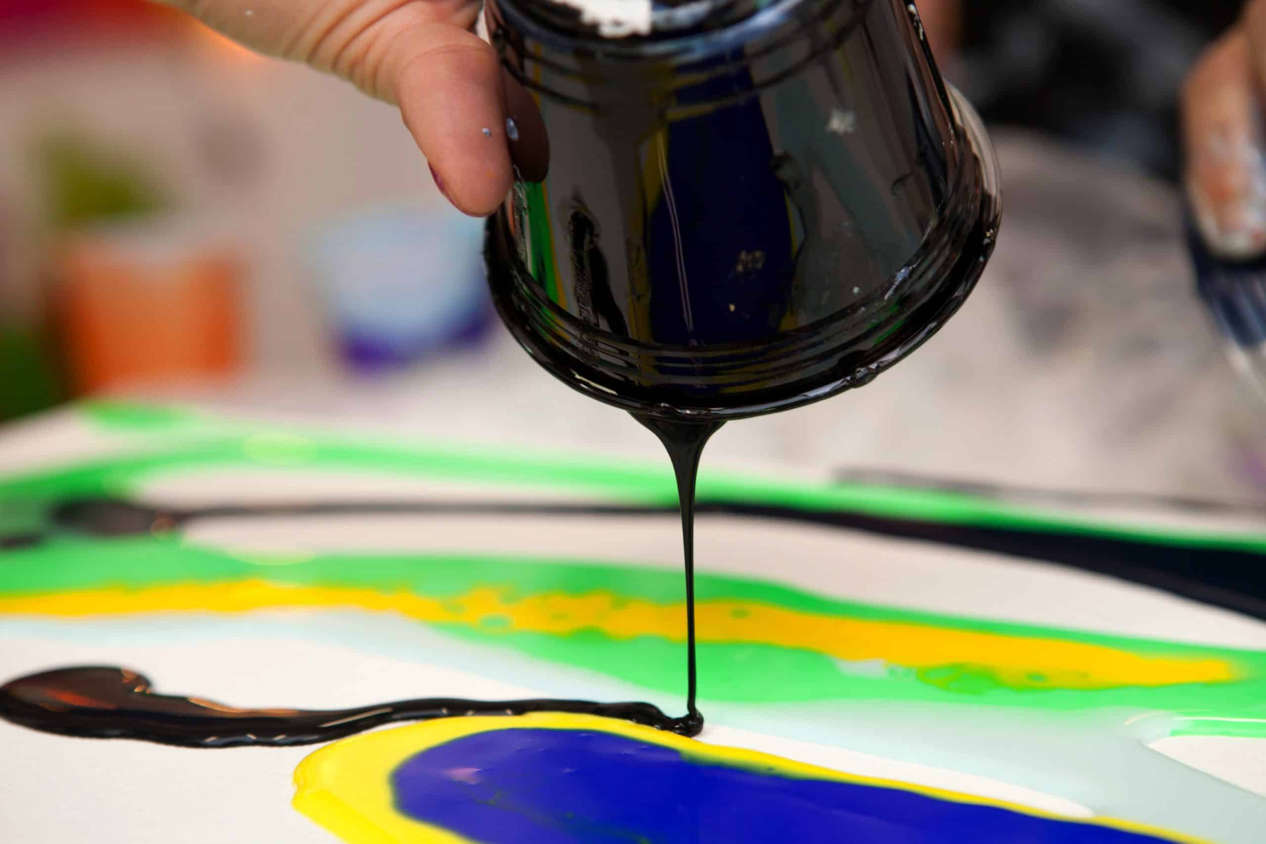 A person pours a small stream of black paint from a plastic cup onto a canvas with swirls of green neon and yellow during the process of fluid painting with acrylic paints mixed with floetrol medium.; Shutterstock ID 1420128320; Purchase Order: AD126