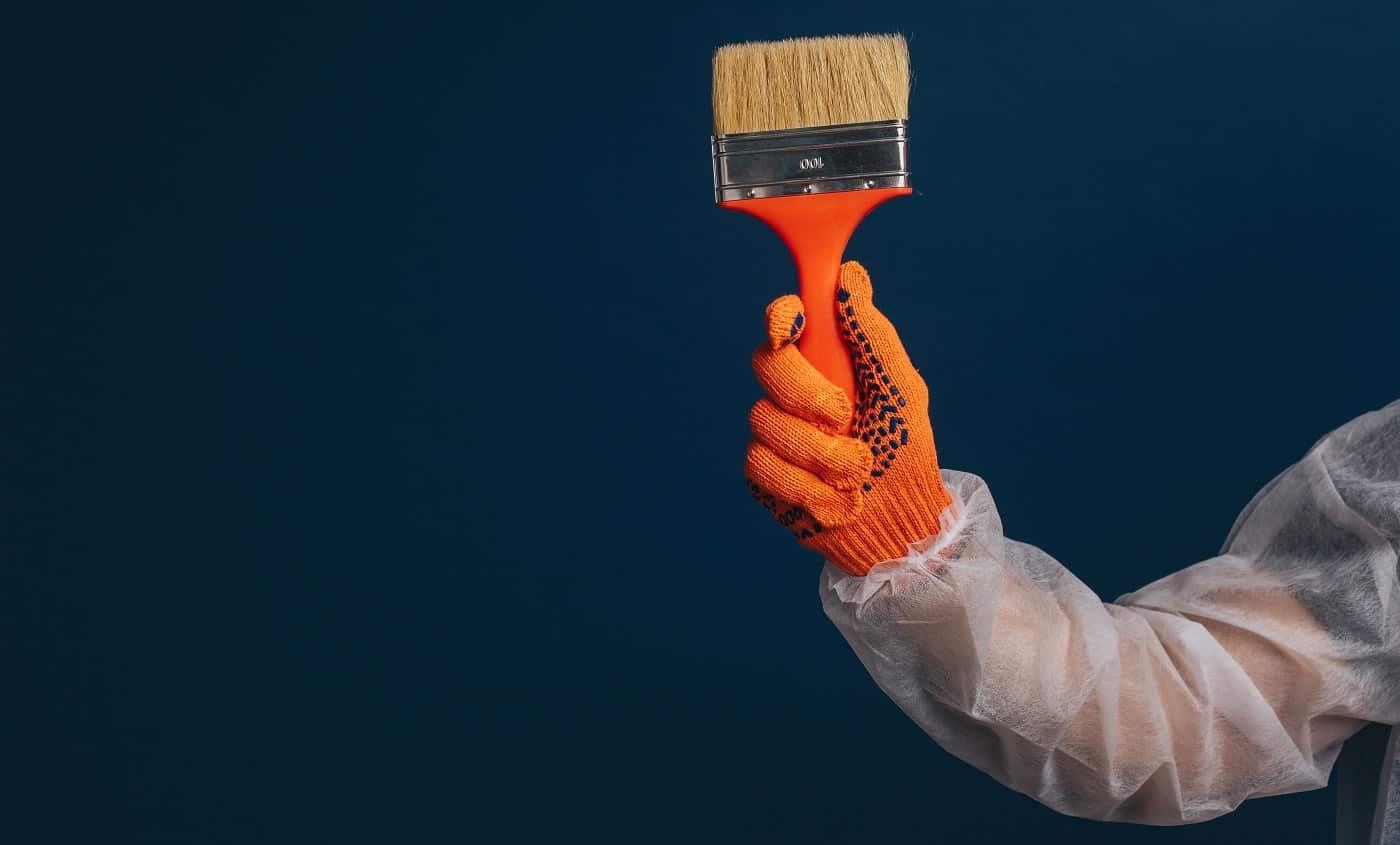 Builder's hand is holding paint brush, isolated over blue background.