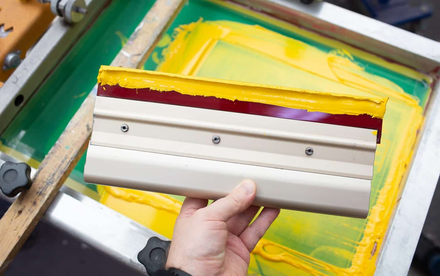 Squeegee for Serigraphy silk screen print process at clothes factory. Frame, squeegee and plastisol color paints.