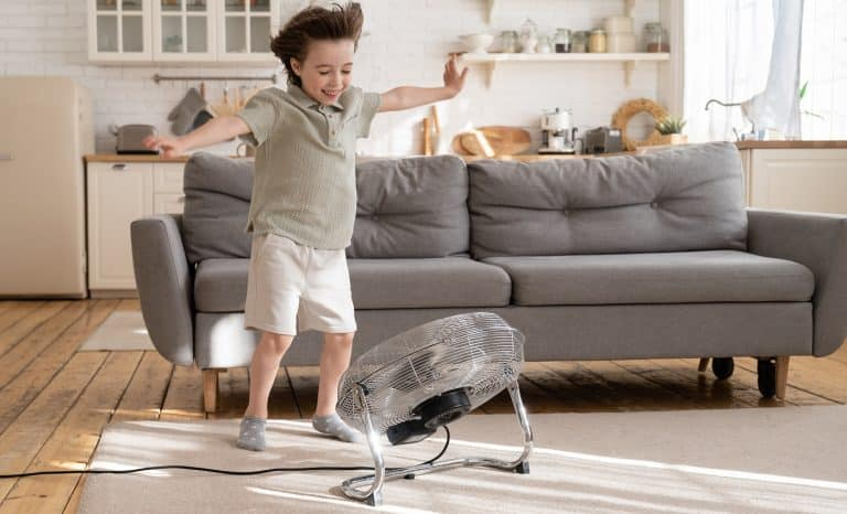 Little boy play with strong wind blow from ventilator or industrial fan at home in cozy living room. Small kid alone with retro air conditioner enjoy refreshing fresh breeze. Child has fun with cooler