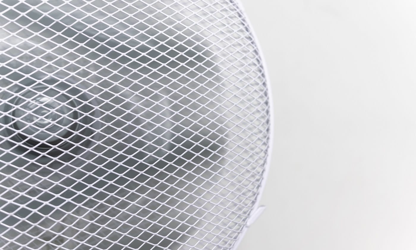 a white fan blows against the background of a white wall. A fan with a grid is located at home in office and cools. Summer heat. Escape from heat. climate system. fan with space for text copy space.