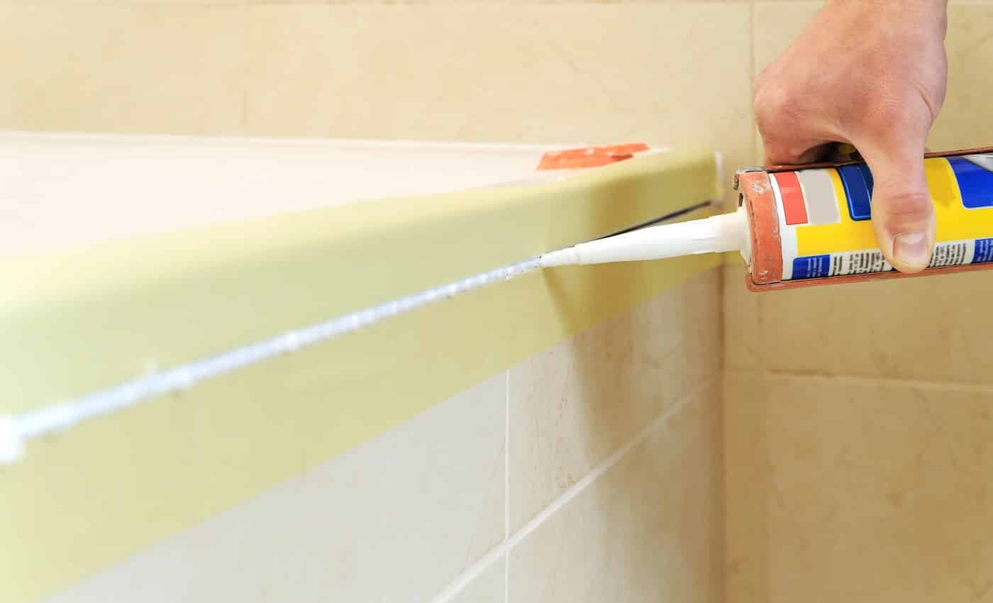 Worker puts silicone sealant to caulk the joint between tub and wall.