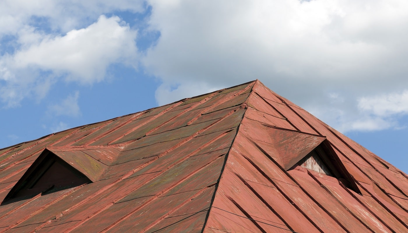 old red metal roof of the building against the blue sky, a lot of damage on the metal, closeup