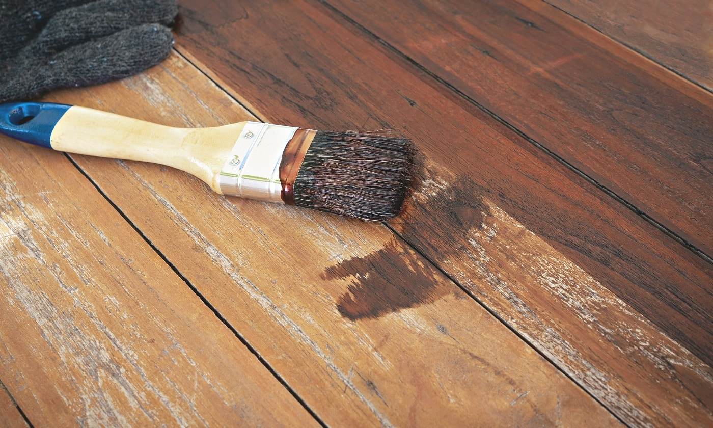 paintbrush and gloves put on wood table.