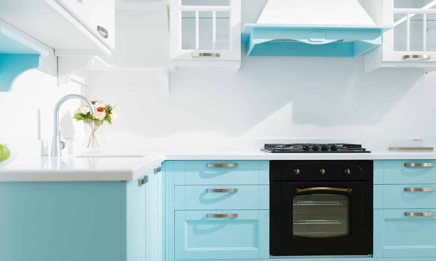 Luxury kitchen interior in white and blue tones, nobody. Modern domestic furniture, sink with faucet, range hood, built-in stove and oven, design of cooking place