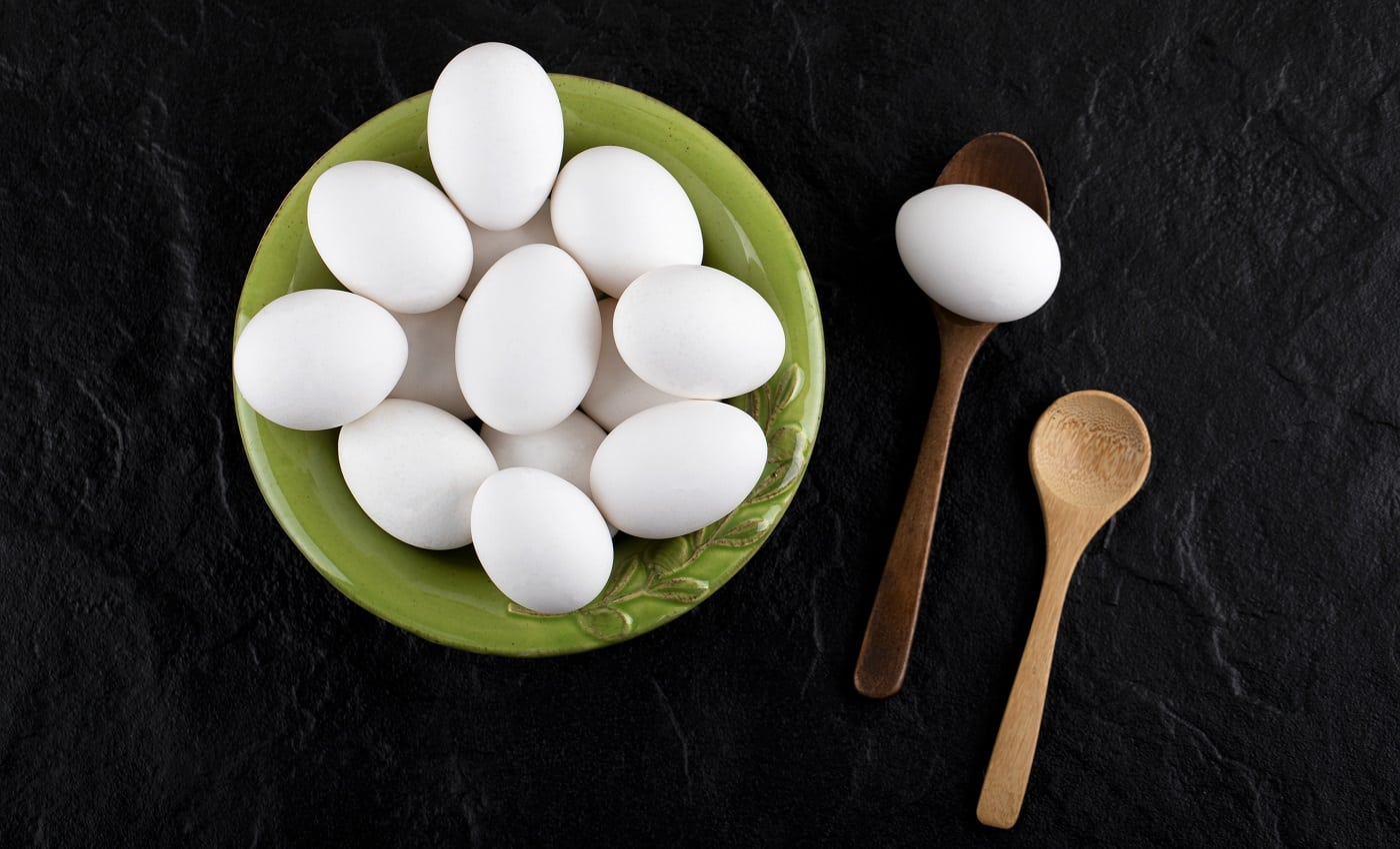Bunch of raw eggs on green plate with wooden spoons. High quality photo