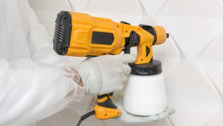 The painter is painting a 3d wall with a spray gun.