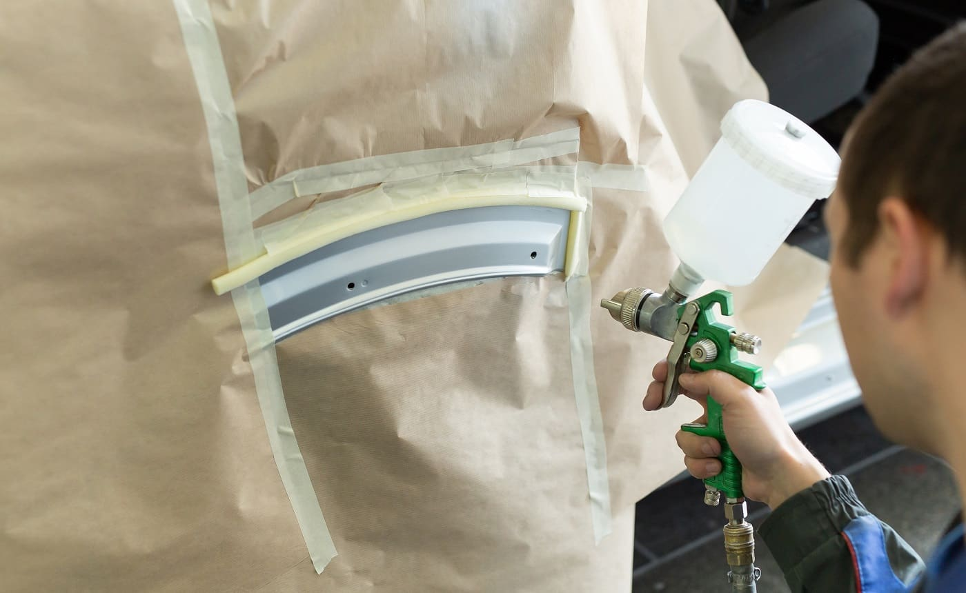 Close-up of a spray gun with white paint for painting a car in a special booth.