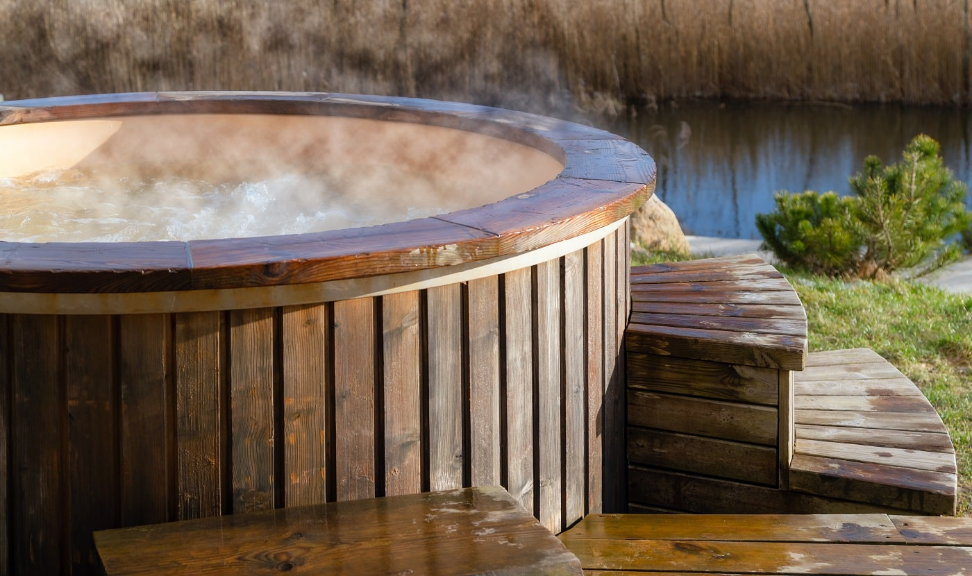 How water swirling in wooden hot tub outside in nature. Enjoying hot steaming pool on a sunny day, private spa treatment. Nobody