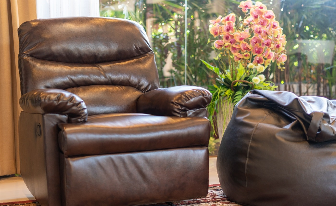 Interior design of house, home, villa feature leather couch,bean bag, artificial flower and a view of garden from living room