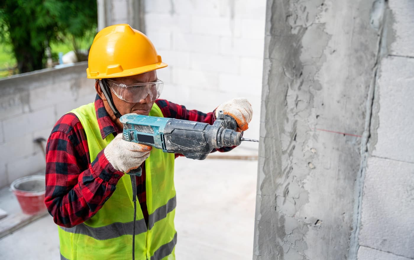 tiler using electric impact drill to drilling cement wall at unfinished house construction