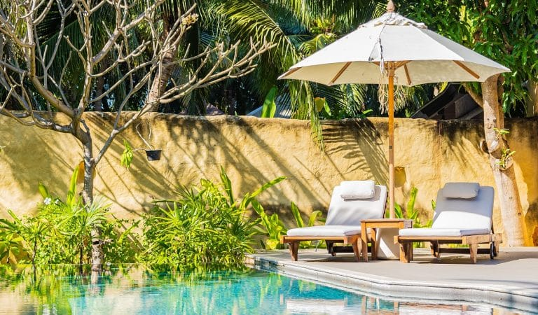 Umbrella and chair around outdoor swimming pool in resort hotel for vacation leisure