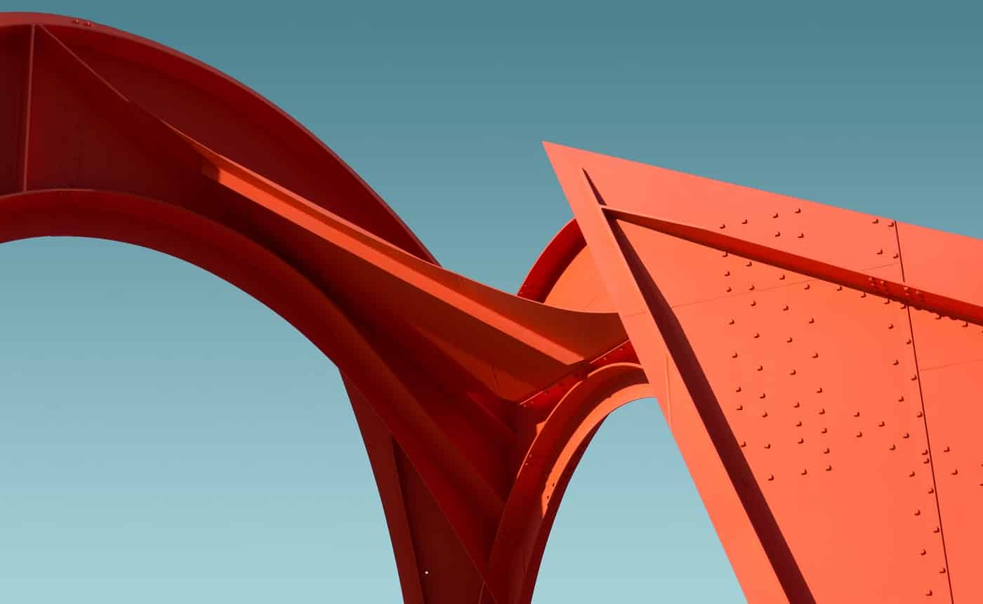 A low angle shot of a metal red structure under the clear blue sky