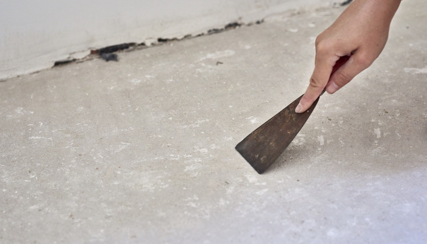 Person with a scraper removes the imperfection from the floor for installing laminate wood. Floor repair inside the room
