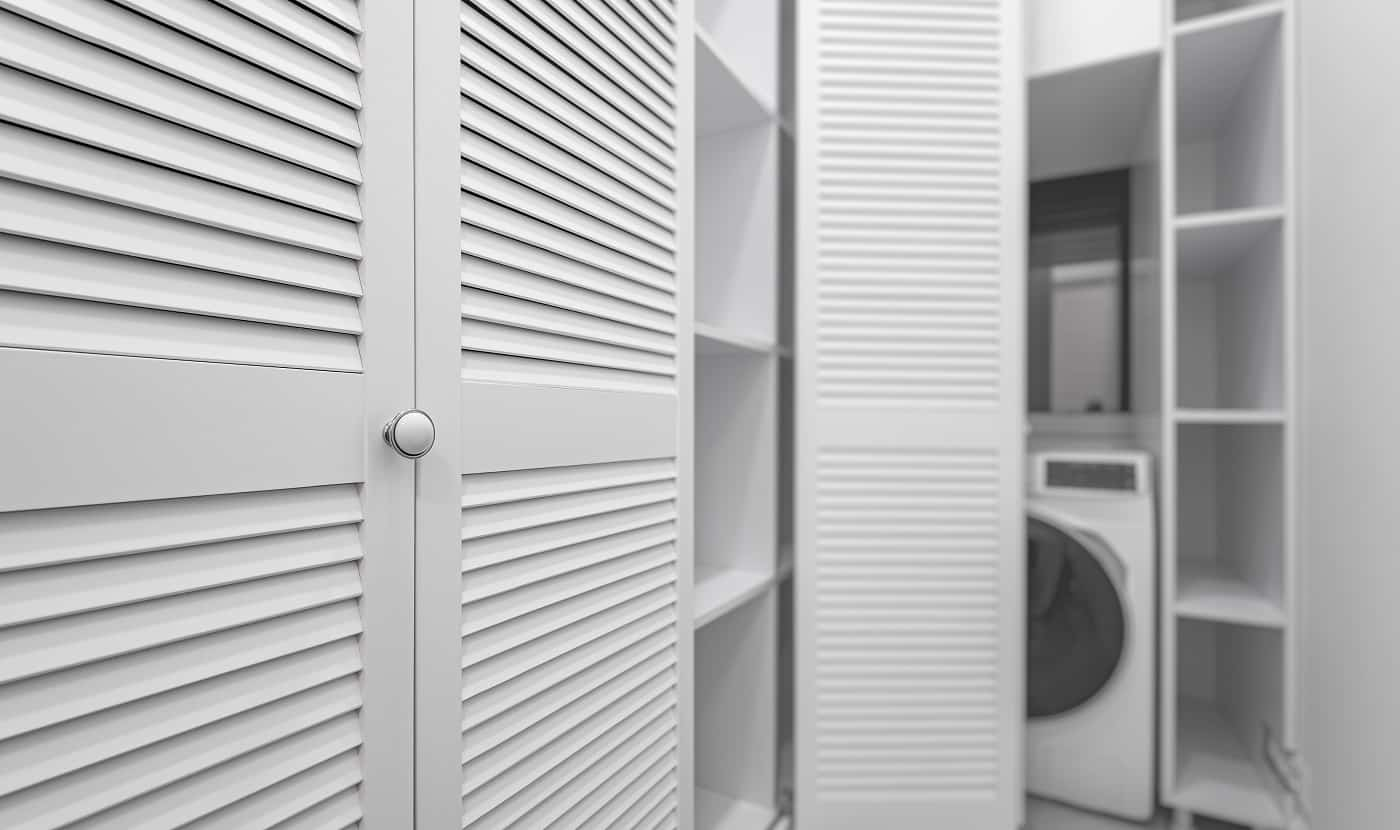 White wardobe room with washing machine in new luxury apartment, focus at foreground left, background right is defocused