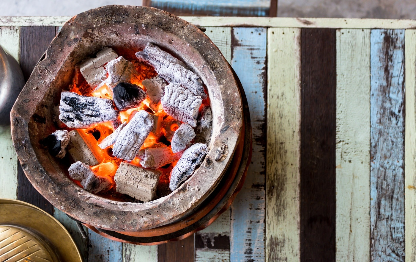 Burning charcoal with flame in the baked clay stove on the wooden table