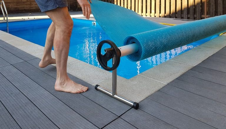 Man covers swimming pool with cover for protection against dirt, leaves, heating and cooling water.