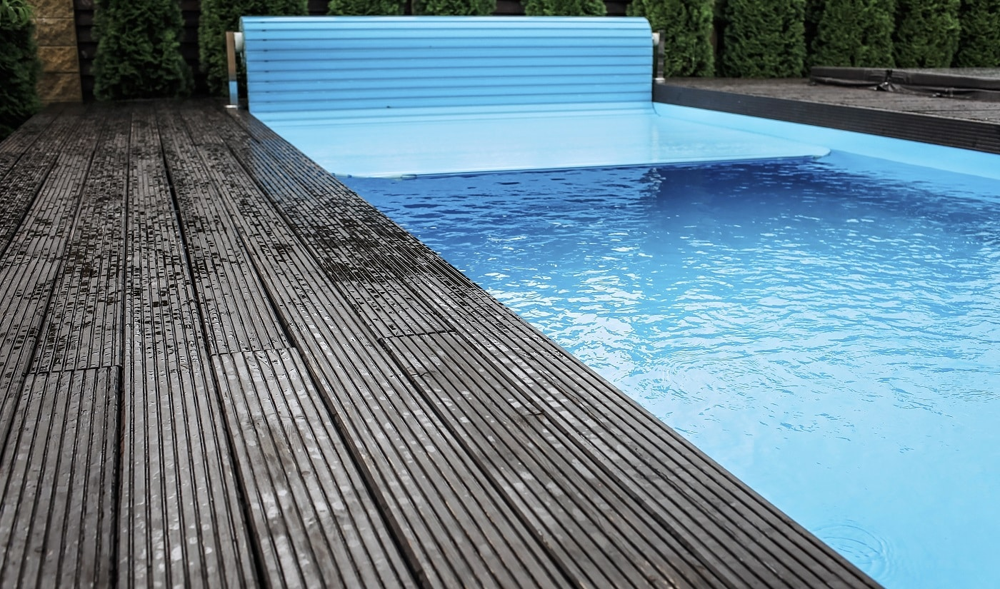 Automatic swimming pool covering system, safely protect children and pets from accidental contact with water, home and cottage equipment, copyspace, place for text, outdoor exterior
