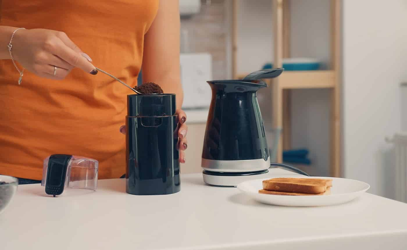 Housewife putting coffee in electric pot during breakfast. Housewife at home making fresh ground coffee in kitchen for breakfast, drinking, grinding coffee espresso before going to work