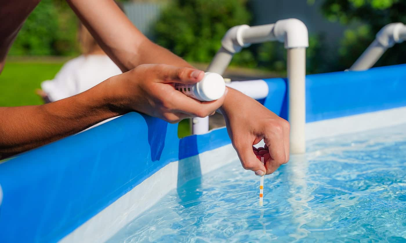 Checking the water quality of a pool with the help of a test strip with PH value, chlorine and algaecide. High quality photo