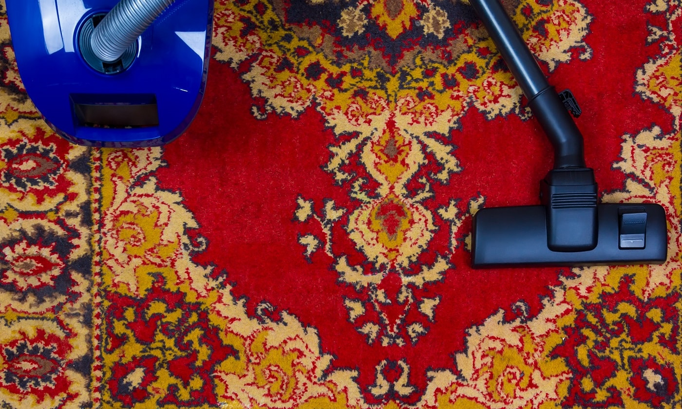 electric vacuum cleaner on the background of an old carpet, top view of flat lay
