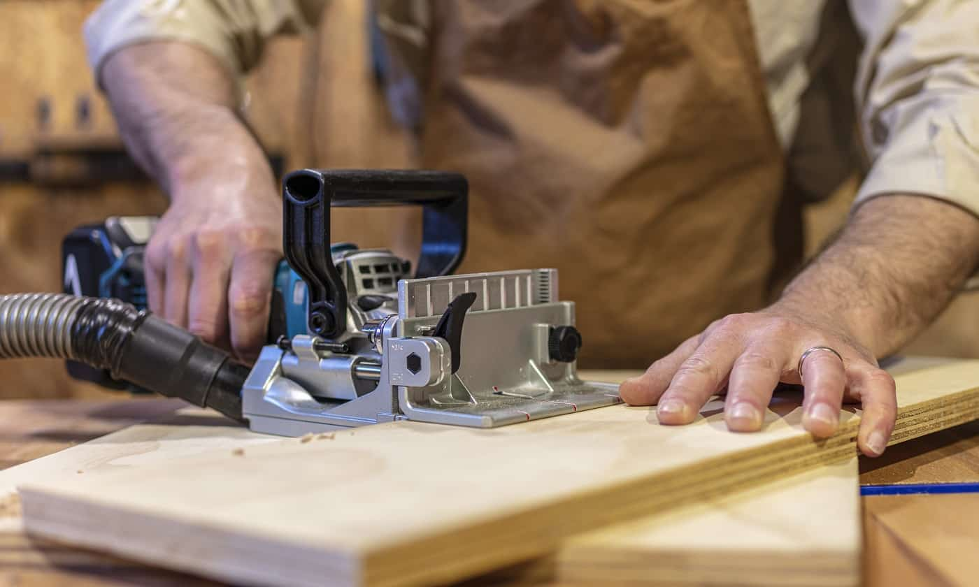detail of biscuit jointer at work on a plywood board
