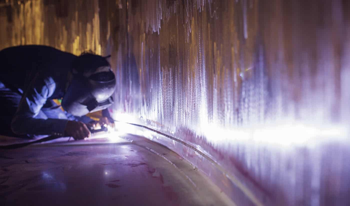 Welding arc argon worker male repaired metal is welding sparks industrial construction tank stainless oil inside confined spaces.