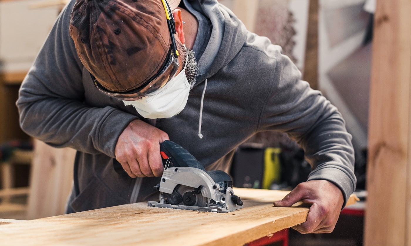 Carpenter with face mask cutting a plank of wood with a electric circular hand saw