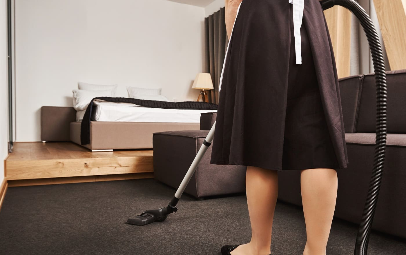 Cropped rearview of female housemaid cleaning floor of living room with vacuum cleaner, being busy and in hurry to finish before owner will come home, trying to remove all dirt and make apartment neat.