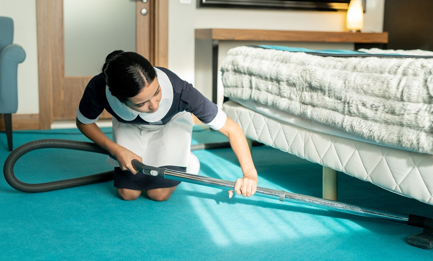 Young beautiful brunette chambermaid in uniform using vacuum cleaner while cleaning blue floor covering under bed in hotel room