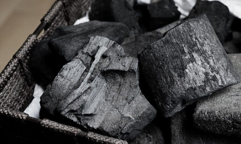 Black Charcoal on black textured floor. charcoal black carbon reesidue produced by strongly heating wood. Used for cooking or other industries. Natural wood charcoal. traditional hard wood charcoal.