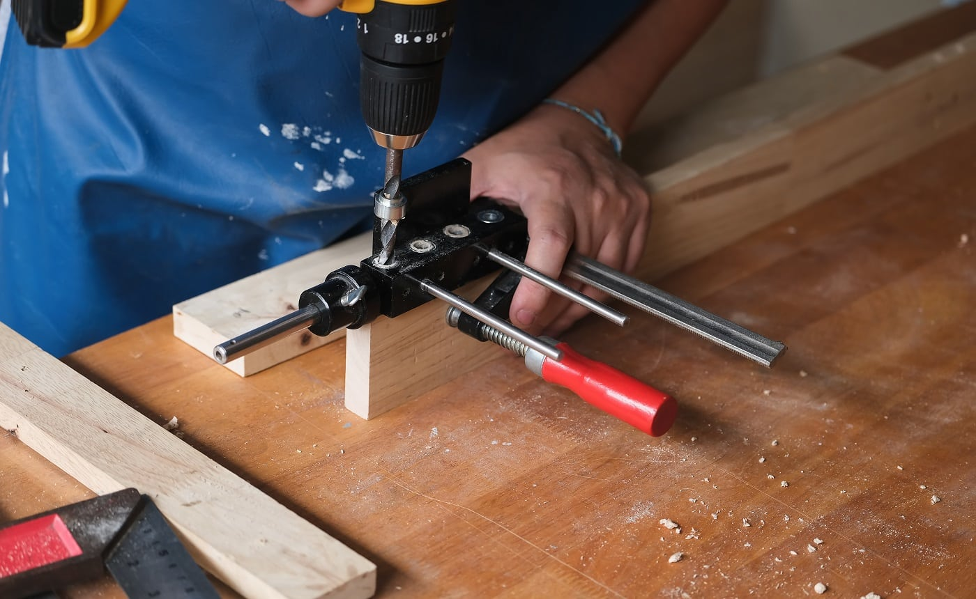 Woodworking entrepreneurs are using a drill through the wood holes to assemble and build wooden tables for customers.