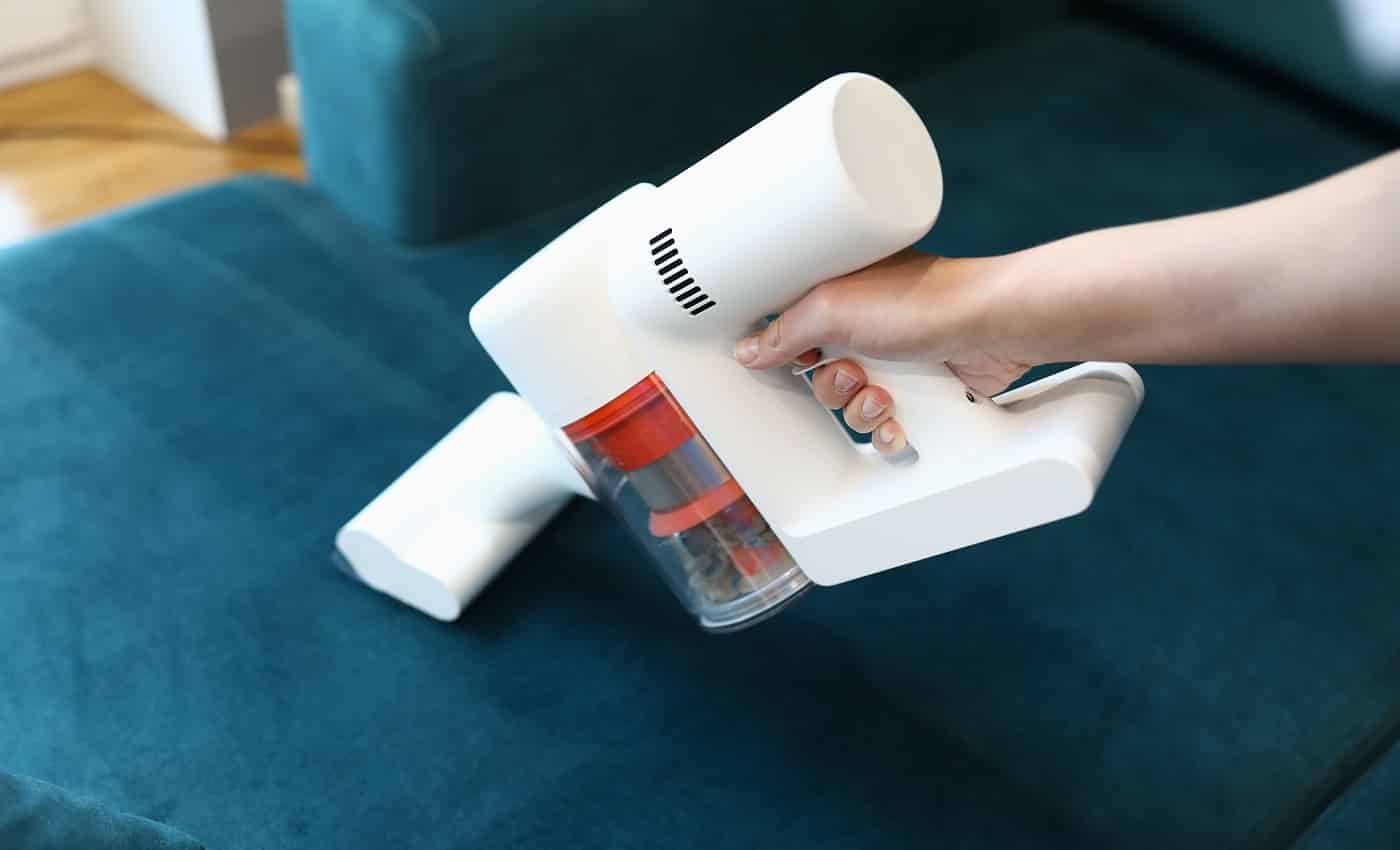 Close-up of womans hand cleaning green sofa with small white compact vacuum cleaner. Renovation and interior design. Housewife or cleaning service concept