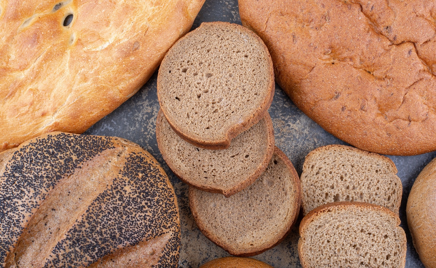Variety of bread types bundle together on marble background. High quality photo