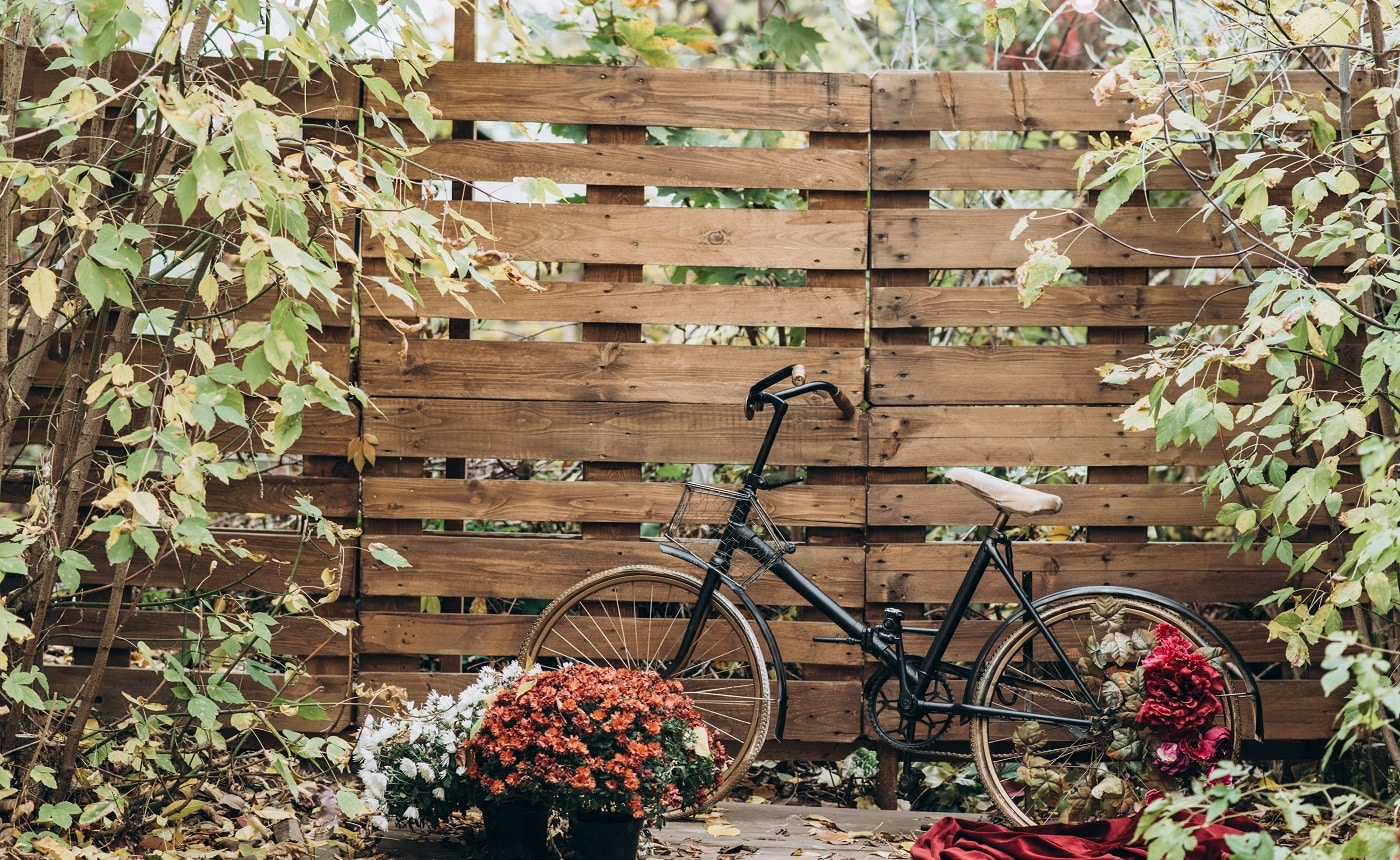Vintage wooden fence covered with autumn leaves and a bicycle standing nearby at the autumn yard. Seasons concept. Stock photo
