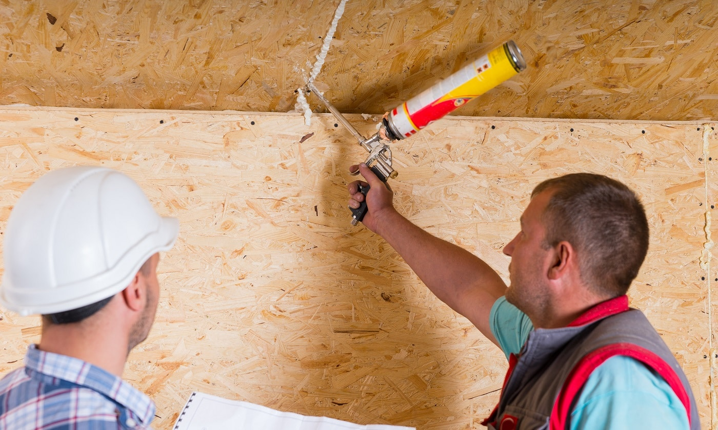 Construction Site Foreman Wearing White Hard Hat Holding Plans and Observing Worker Applying Caulking to Unfinished Wood Ceiling