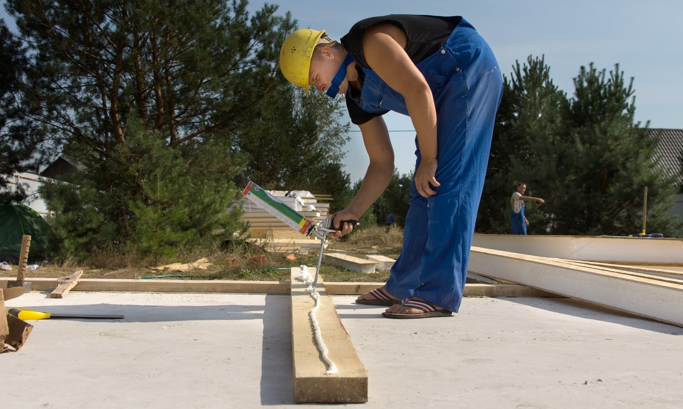 Builder or carpenter applying glue to a wooden beam on a construction site from a glue gun